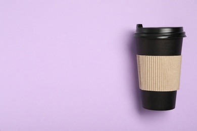 Takeaway paper coffee cup with cardboard sleeve on violet background, top view. Space for text