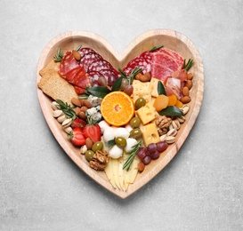 Heart shaped plate with different delicious snacks on grey table, top view