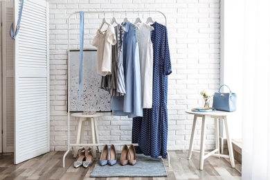 Wardrobe rack with women's clothes and different shoes at white brick wall in room