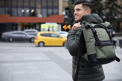 Male tourist with travel backpack on city street. Urban trip