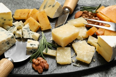 Cheese platter with specialized knives and fork on table, closeup view