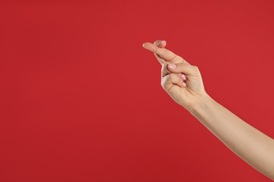 Woman holding fingers crossed on red background, closeup with space for text. Good luck superstition