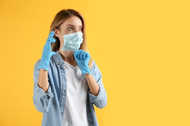 Young woman in medical gloves putting on protective face mask against yellow background. Space for text
