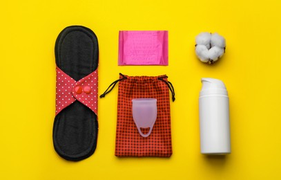Cloth menstrual pad and other female hygiene products on yellow background, flat lay