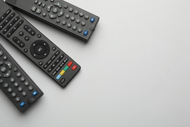 Remote controls on light grey background, flat lay. Space for text
