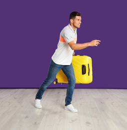 Man with suitcase for summer trip running on purple background. Vacation travel