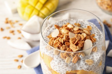 Delicious chia pudding with granola and mango in glass on table, closeup