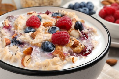 Tasty oatmeal porridge with toppings on table, closeup