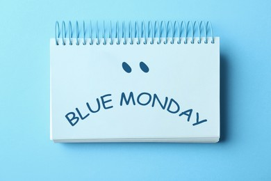 Notebook with text Blue Monday on color background, top view