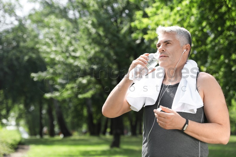 Handsome mature man with bottle of water in park, space for text. Healthy lifestyle