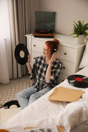Young woman listening to music with turntable in bedroom