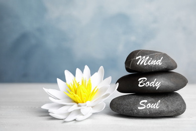 Stones with words Mind, Body, Soul and lotus flower on white wooden table. Zen lifestyle