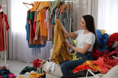 Happy young woman with lots of clothes on sofa in room. Fast fashion