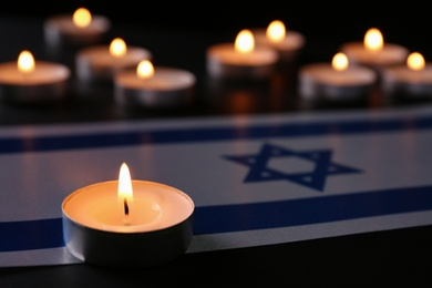 Burning candle and flag of Israel on black table. Holocaust memory day