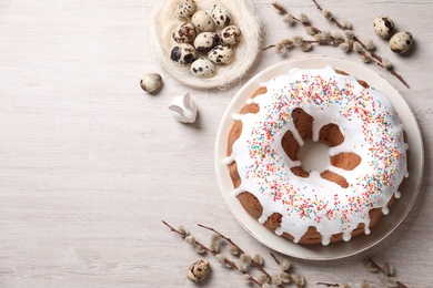 Glazed Easter cake with sprinkles, decorative bunny, quail eggs and willow branches on white wooden table, flat lay. Space for text