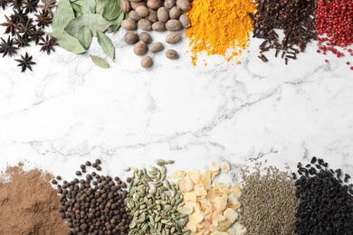Many different spices on white marble background, top view. Space for text