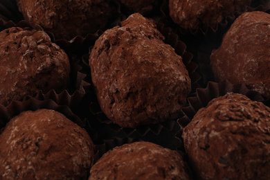 Many delicious chocolate truffle candies as background, closeup