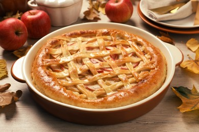 Delicious homemade apple pie and autumn leaves on wooden table. Thanksgiving Day celebration