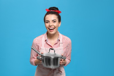 Housewife with pan on light blue background