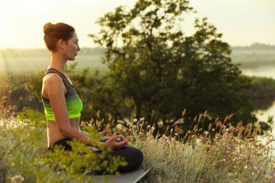 Woman meditating in meadow. Space for text