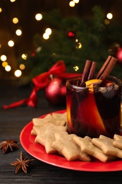 Aromatic mulled wine and cookies on wooden table, closeup