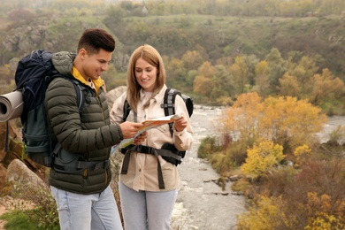 Couple of travelers with backpacks and map planning trip in mountains. Autumn vacation