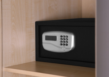Black steel safe with electronic lock on wooden shelf
