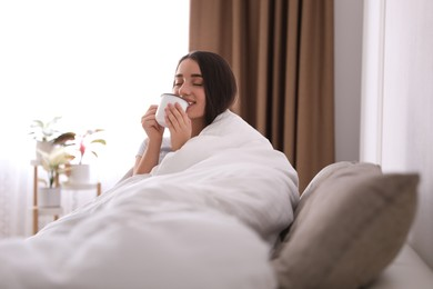 Woman covered in blanket drinking cup of hot beverage on sofa