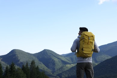 Tourist with backpack enjoying mountain landscape, back view. Space for text