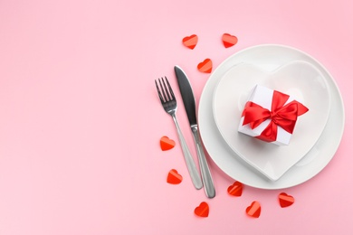 Beautiful table setting on pink background, flat lay with space for text. Valentine's Day dinner