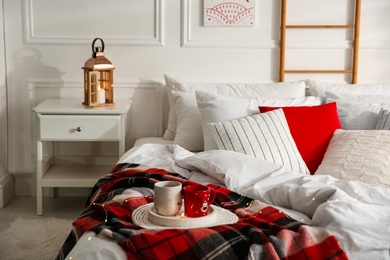 Christmas bedroom interior with red woolen blanket and decorative lantern