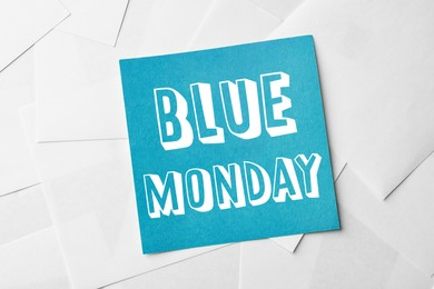 Note with phrase Blue Monday on paper sheets, top view