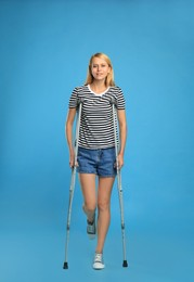 Young woman with axillary crutches on light blue background