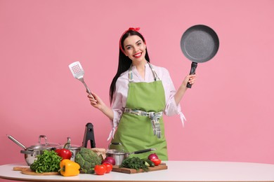 Young housewife with pan, spatula and products on pink background