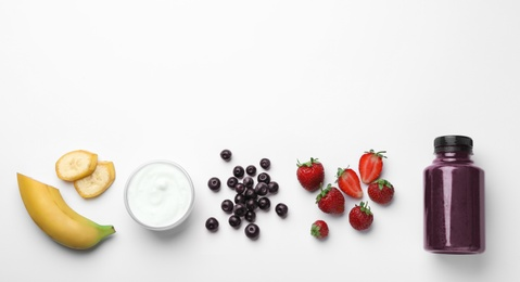 Bottle of acai drink and ingredients on white background, top view