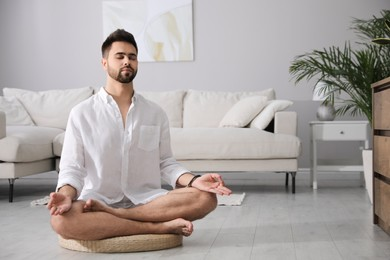 Young man meditating on straw cushion at home, space for text