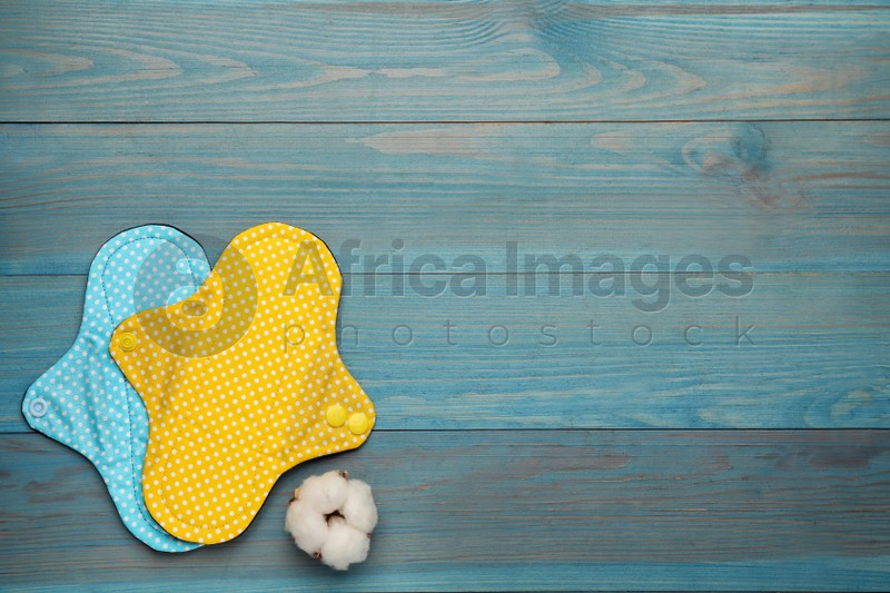 Reusable cloth menstrual pads and cotton flower on light blue wooden table, flat lay. Space for text