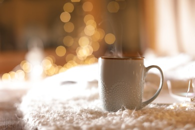 Cup of hot beverage on fuzzy rug against blurred background, space for text. Winter evening