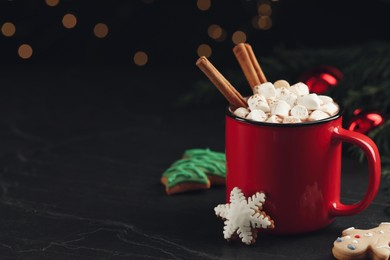 Delicious hot chocolate with marshmallows, cinnamon and gingerbread cookies on black table against blurred lights, space for text