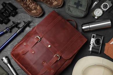 Flat lay composition with leather backpack and camping equipment for tourism on black background