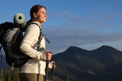 Tourist with backpack and trekking poles enjoying mountain landscape, space for text