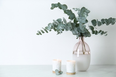 Beautiful eucalyptus branches and burning candles on grey table, space for text. Interior element