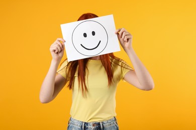 Woman hiding behind sheet of paper with happy face on yellow background