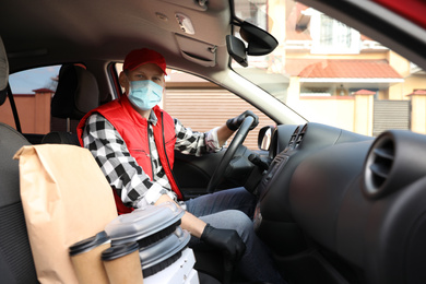 Courier in protective mask and gloves with orders inside car. Food delivery service during coronavirus quarantine