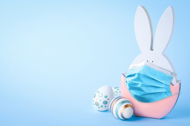 COVID-19 pandemic.COVID-19 pandemic. Easter bunny figure in protective mask on light blue background, space for text