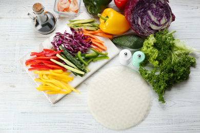 Dry rice paper and ingredients on white wooden table, flat lay