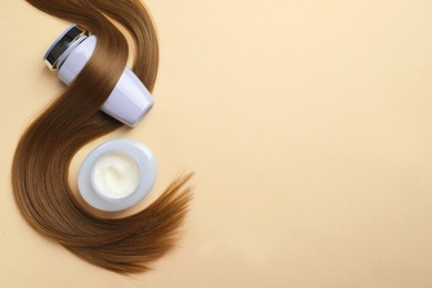 Natural cosmetic products and hair lock on beige background, flat lay. Space for text