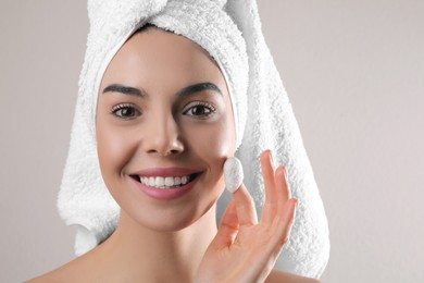 Woman using silkworm cocoon in skin care routine on light grey background. Space for text