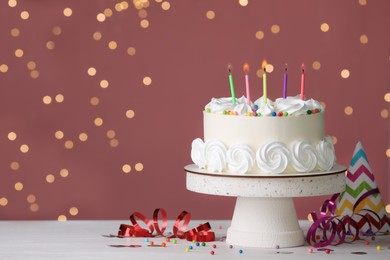 Birthday cake with burning candles and decor on white table against blurred festive lights, space for text