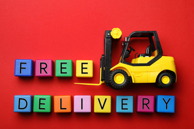 Flat lay composition of toy forklift and words FREE DELIVERY on red background. Logistics and wholesale concept